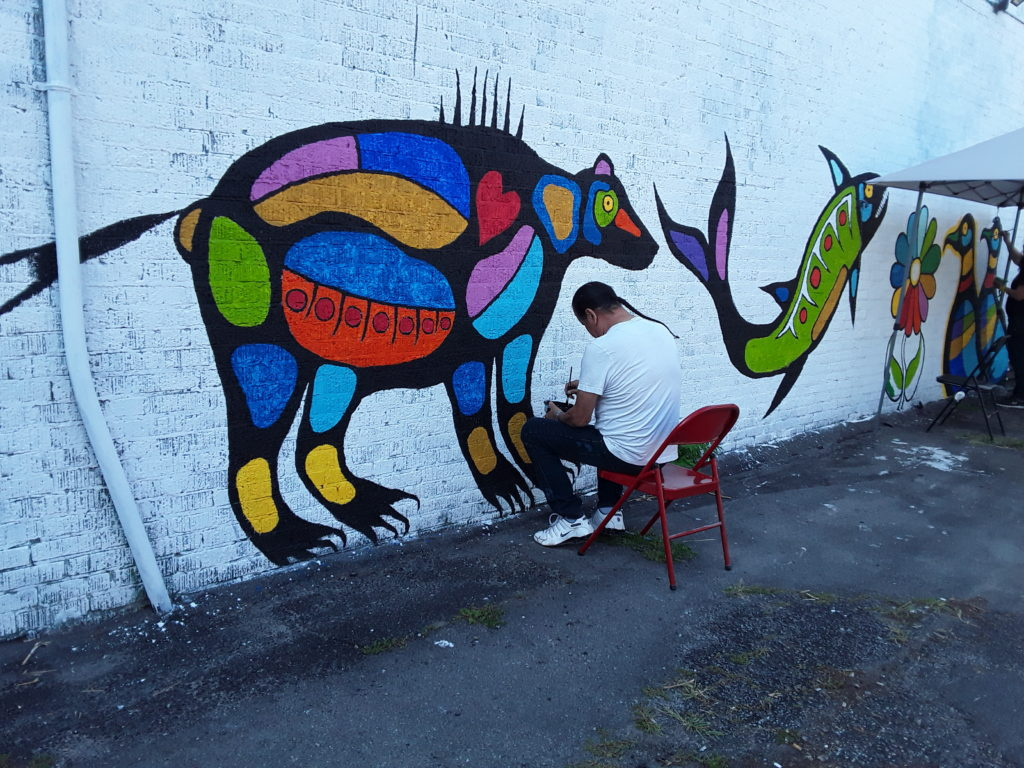 Artist seated in front of white brick wall that features animal spirits painted in the Woodland style.