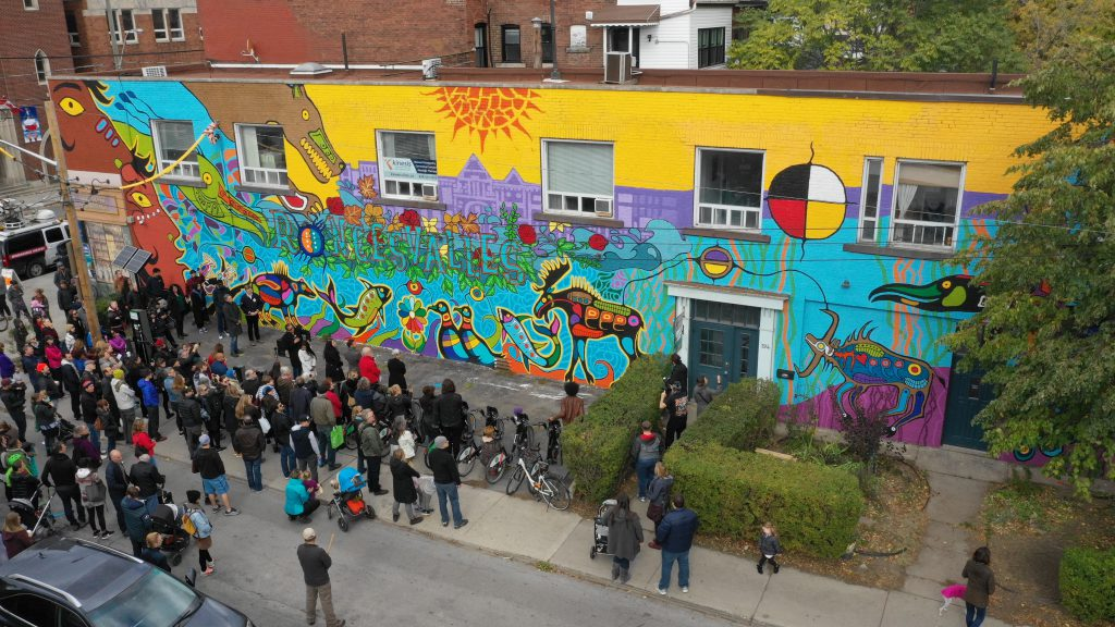 Crowd looking over the mural which features Woodlands style animals and symbols by Philip Cote and the word Roncesvalles intertiwned with foliage by Jim Bravo