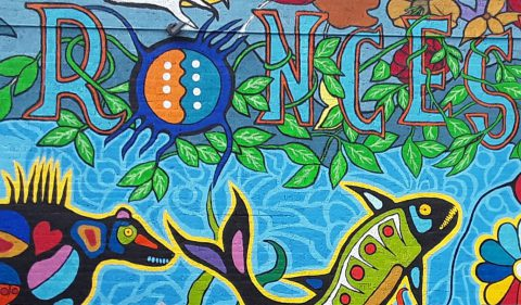 Bear, fish, flower and power symbols painted in Woodlands style.
