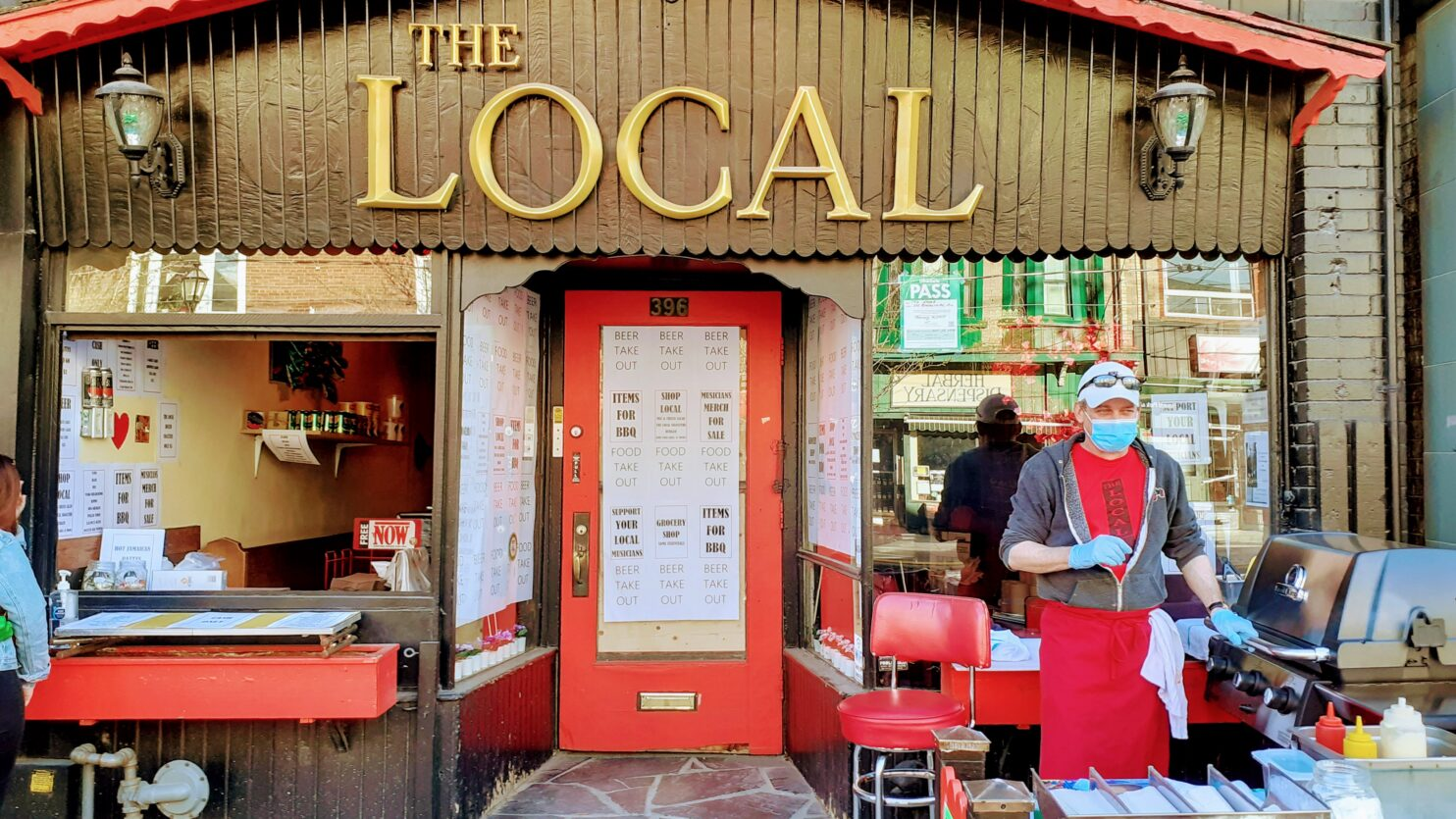 Masked chef prepares food in front of local pub, called The Local, during pandemic.